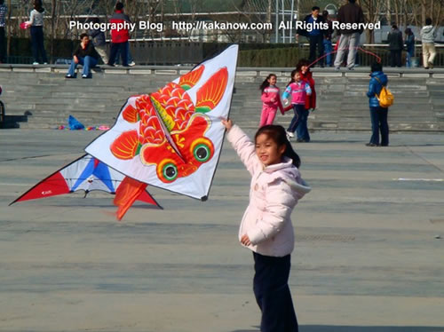 Child kite-flying in spring in Beijing China. Photo by KaKa.