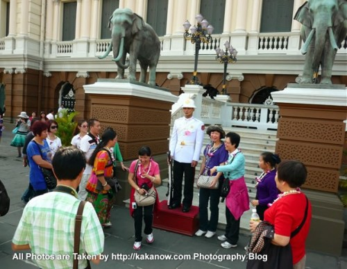 Thailand travel, Bangkok, Grand Palace. Tourists take photo with guard. Photo by KaKa.